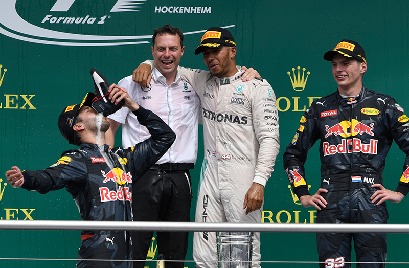 Mercedes driver Lewis Hamilton of Britain, center, and Red Bull driver Max Verstappen, right, watch as Red Bull driver Daniel Ricciardo of Australia drinks sparkling wine from his race driving boot on the podium at the end of the German Formula One Grand Prix in Hockenheim, Germany, Sunday, July 31, 2016. Hamilton won the race, Ricciardo was second and Verstappen was third.