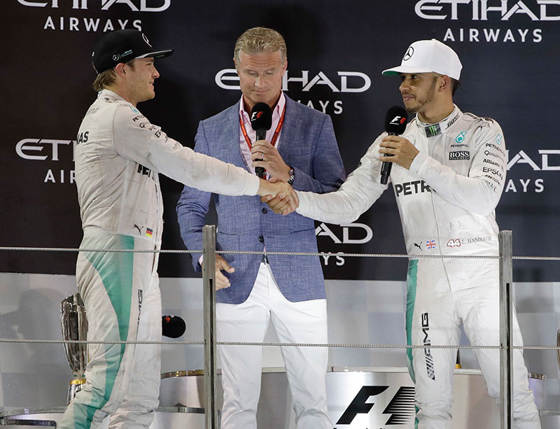 Winner Mercedes driver Lewis Hamilton of Britain, right, cheers second place Mercedes driver Nico Rosberg of Germany, on the podium after the Emirates Formula One Grand Prix at the Yas Marina racetrack in Abu Dhabi, United Arab Emirates, Sunday, Nov. 27, 2016. Rosberg was 12 points ahead of his teammate coming into the title showdown and only needed to finish third, even if Hamilton won.