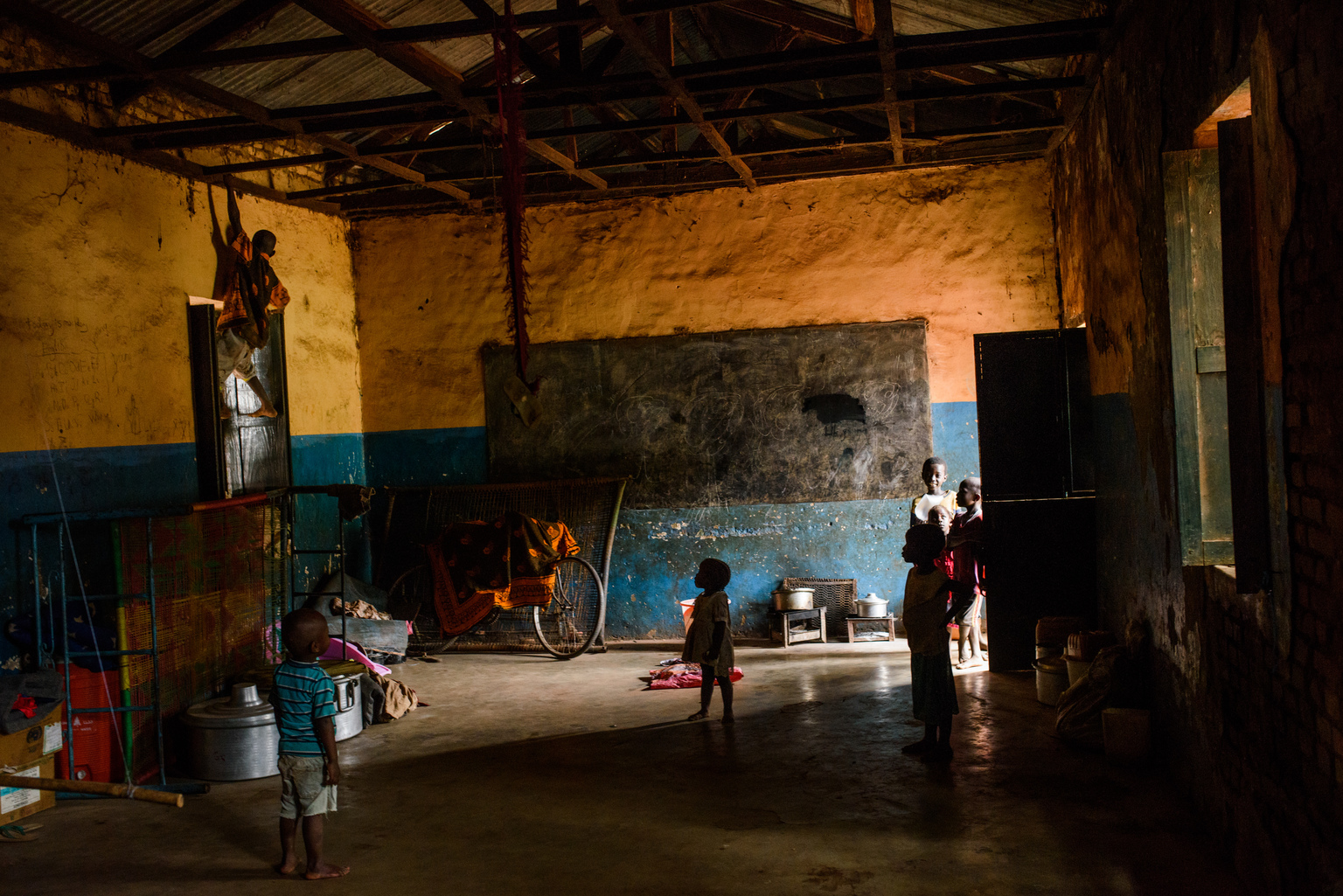 Children play in a classroom which families use as a shelter to sleep in at night, on the grounds of...