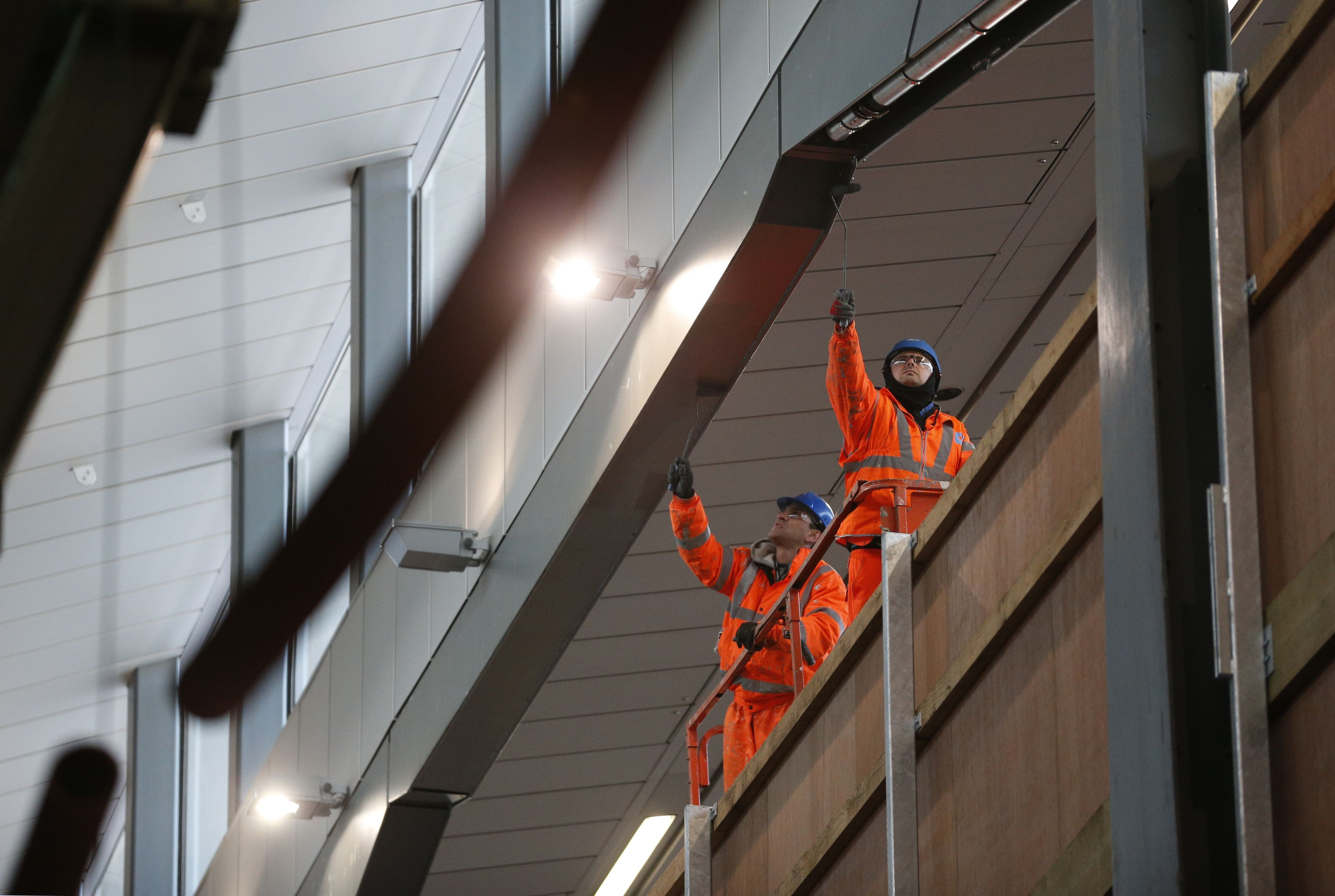 Workers paint steelwork along the new platform ten at London Bridge railway station, Southwark, London as the capital's oldest station undergoes rebuilding as part of the �6.5bn Thameslink Programme. PRESS ASSOCIATION Photo. Picture date: Monday November 24, 2014.  From Saturday 20 December 2014 to Sunday 4 January 2015 inclusive, Southern and Thameslink trains will not call at London Bridge. Also, from Monday 22 to Wednesday 24 December some Southeastern Charing Cross services will not call at London Bridge in the morning peak as work continues. Photo credit should read: Jonathan Brady/PA Wire