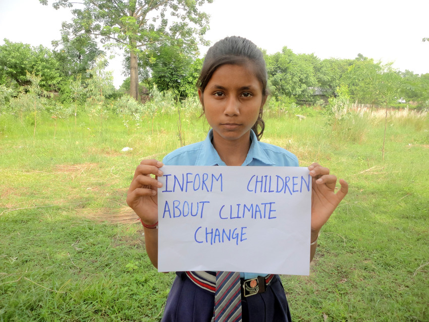 In Nepal, Sanchita, 12, holds a message reading 'Inform children about climate
