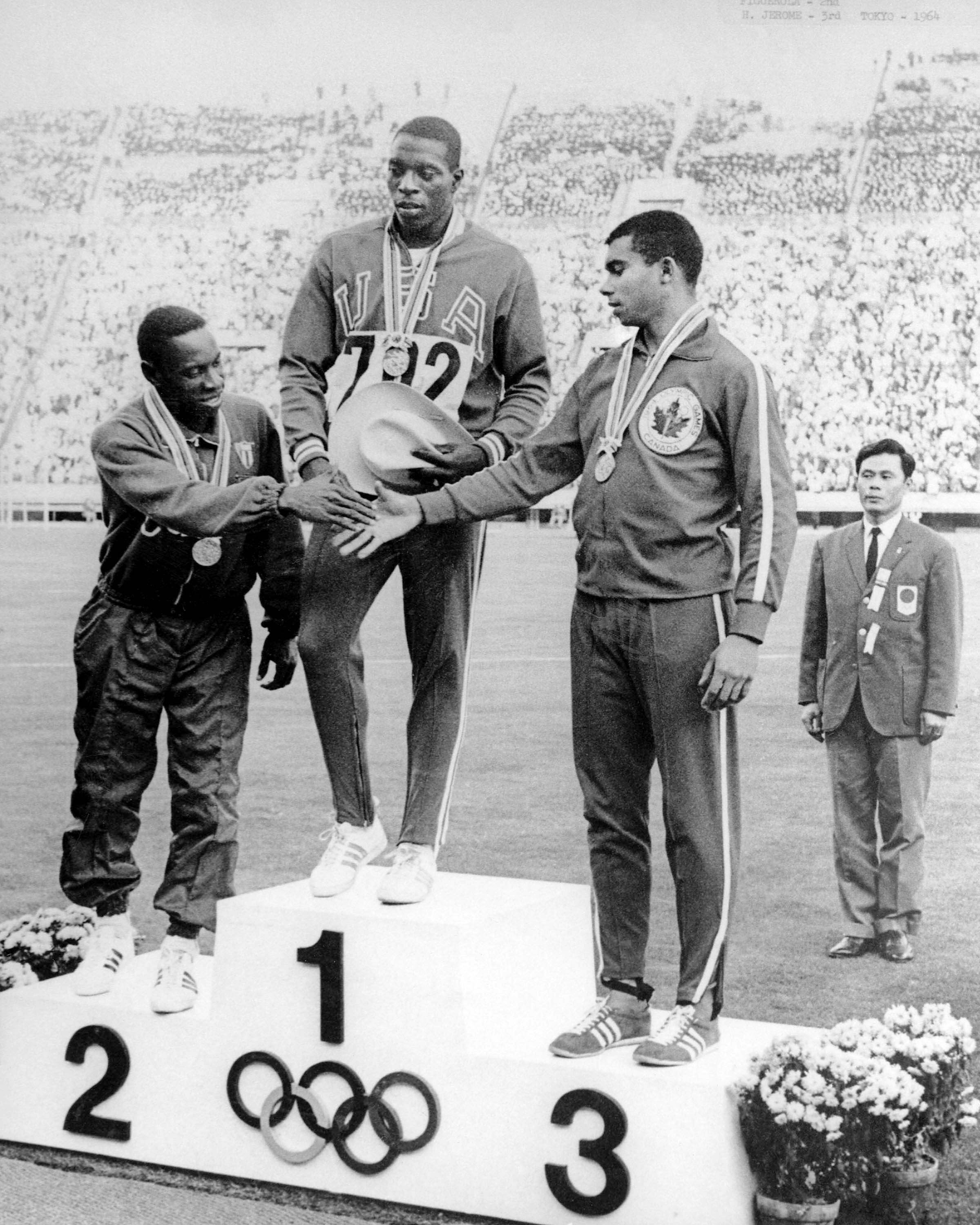 Harry Jerome (right) celebrates his bronze medal win in the 100m athletics event at the 1964 Tokyo
