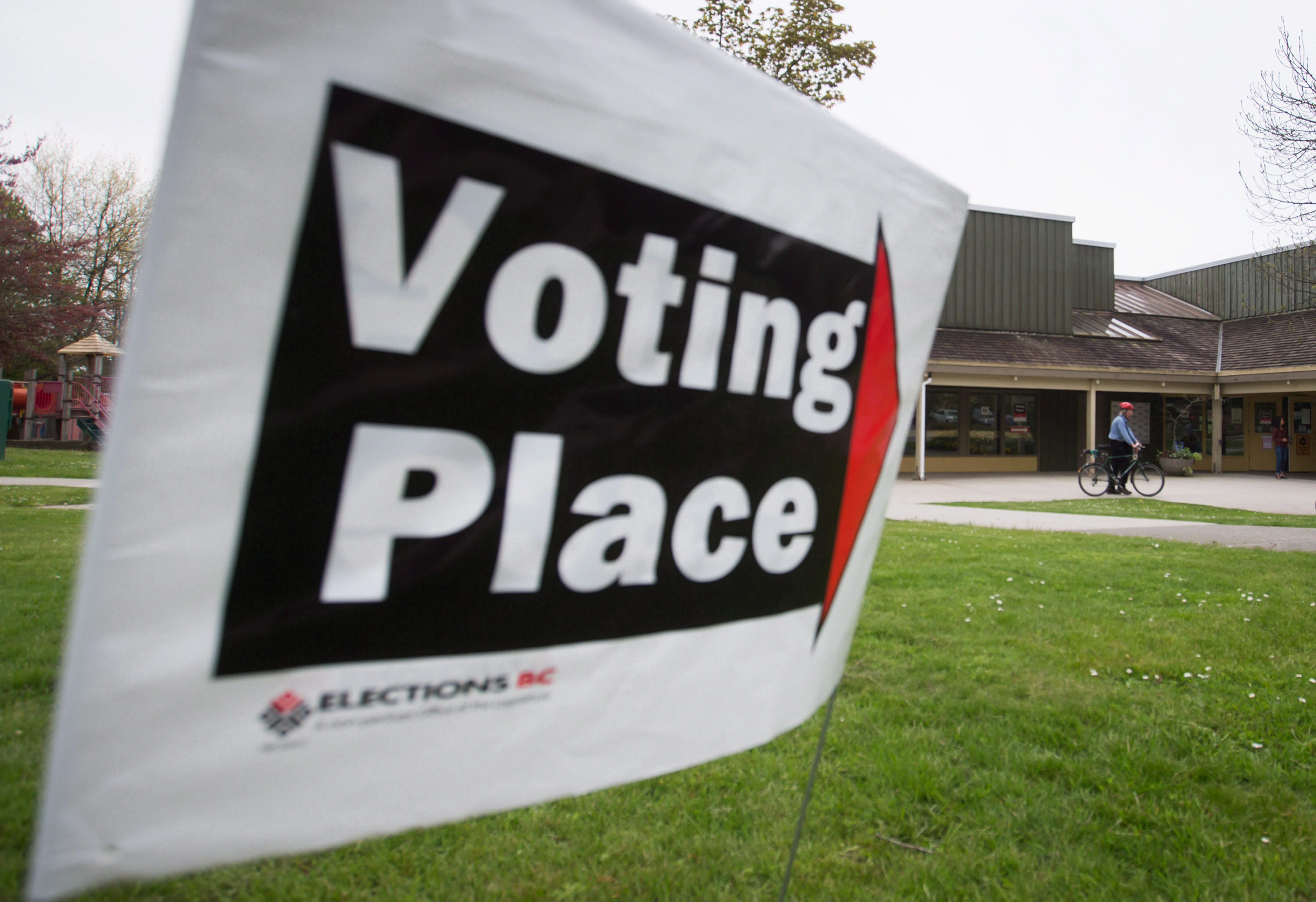 A voter arrives at a polling station on a bike to cast their ballot in the provincial election in the...