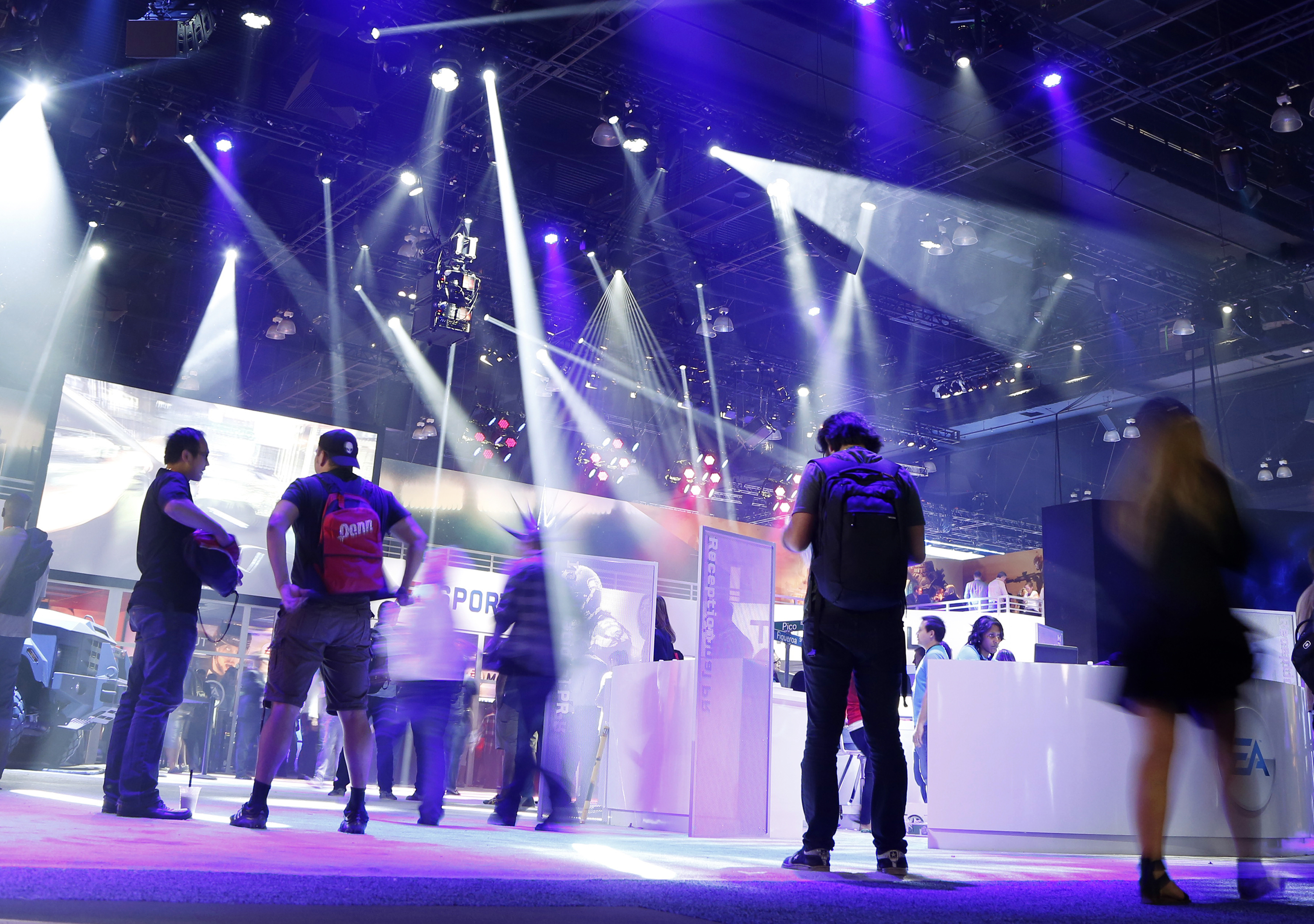People walk in the Electronic Arts booth during the 2014 Electronic Entertainment Expo, known as E3, in Los Angeles, California June 11, 2014.  REUTERS/Jonathan Alcorn   (UNITED STATES - Tags: SCIENCE TECHNOLOGY BUSINESS SOCIETY)