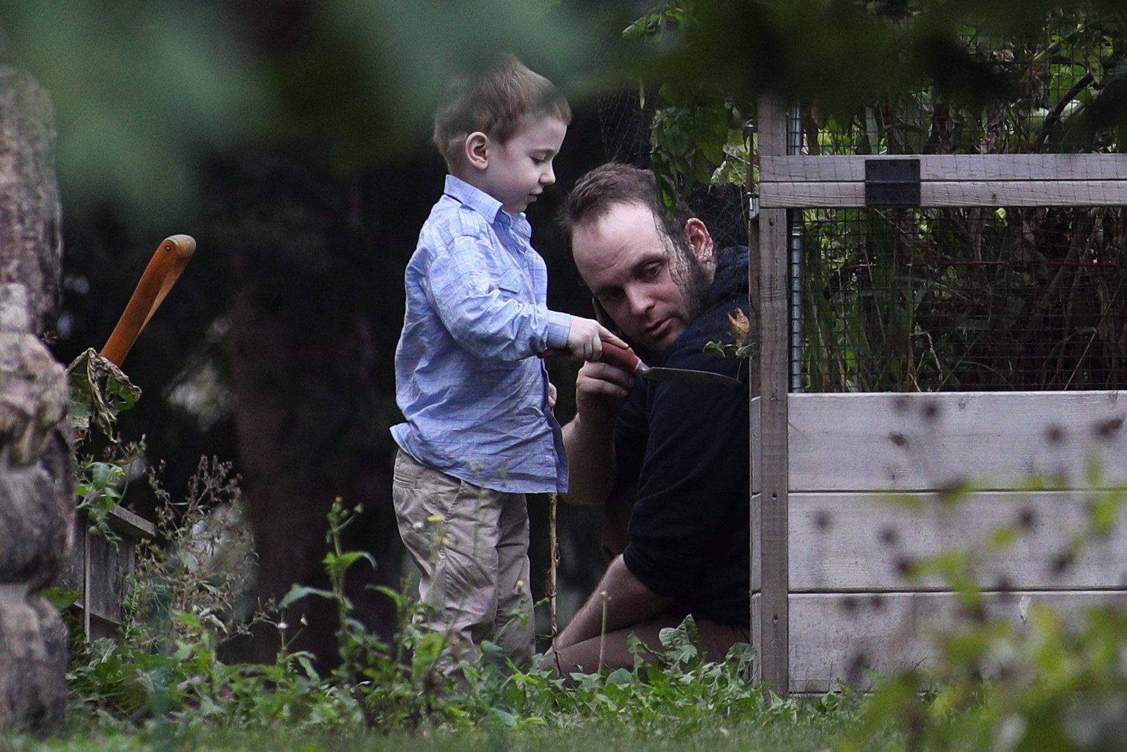 Joshua Boyle and one of his kids play in the garden at his parents' house in Smiths Falls, Ont., on Oct....
