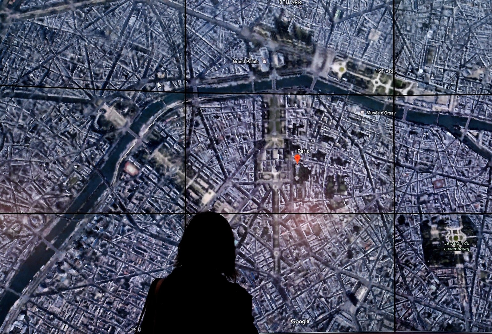 People look at a Google Earth map of Paris,France on a screen as Google Earth unveils the revamped version of the application April 18, 2017 at a event at New York's Whitney Museum of Art.Google on Tuesday launched a re-imagined version of its free Earth mapping service, weaving in storytelling and artificial intelligence and freeing it from apps. / AFP PHOTO / TIMOTHY A. CLARY        (Photo credit should read TIMOTHY A. CLARY/AFP/Getty Images)
