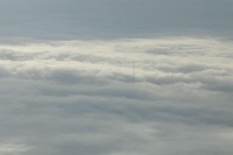 Passenger photographs floating pole outside plane window