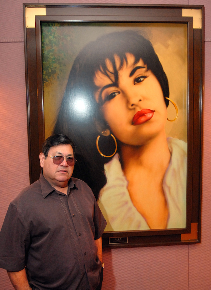 In this June 24, 2011 photo, Abraham Quintanilla, the father of the late singer Selena, poses in front of an air brush work of art that a fan gave him after her death, hanging in the studio at Q Productions in Corpus Christi, Texas, where Selena made her last recording.  (AP Photo/Paul Iverson)
