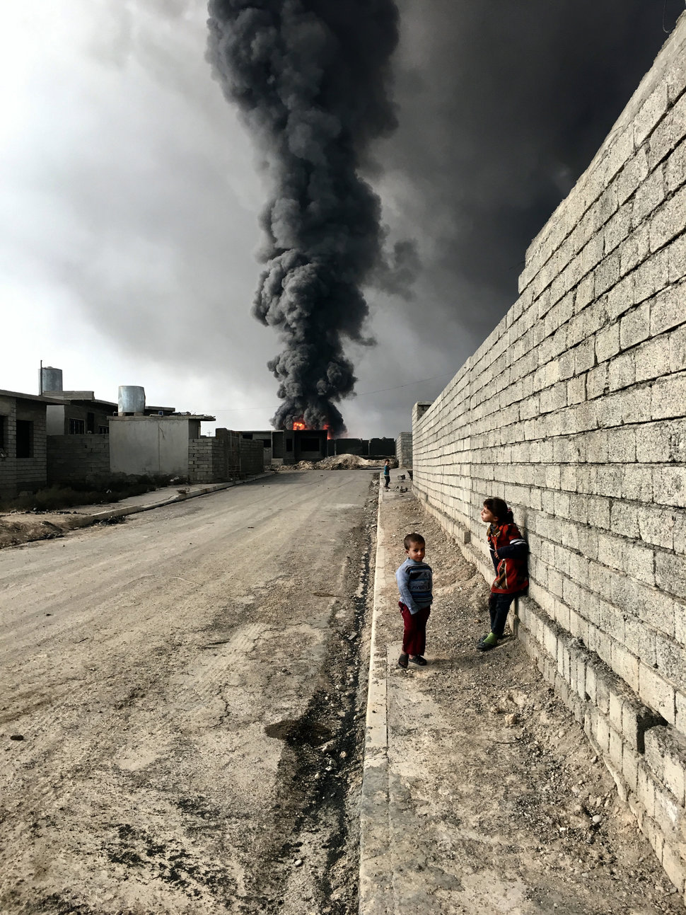 Children roam the streets in Qayyarah near the fire and smoke billowing from oil wells, set ablaze by ISIS militants.