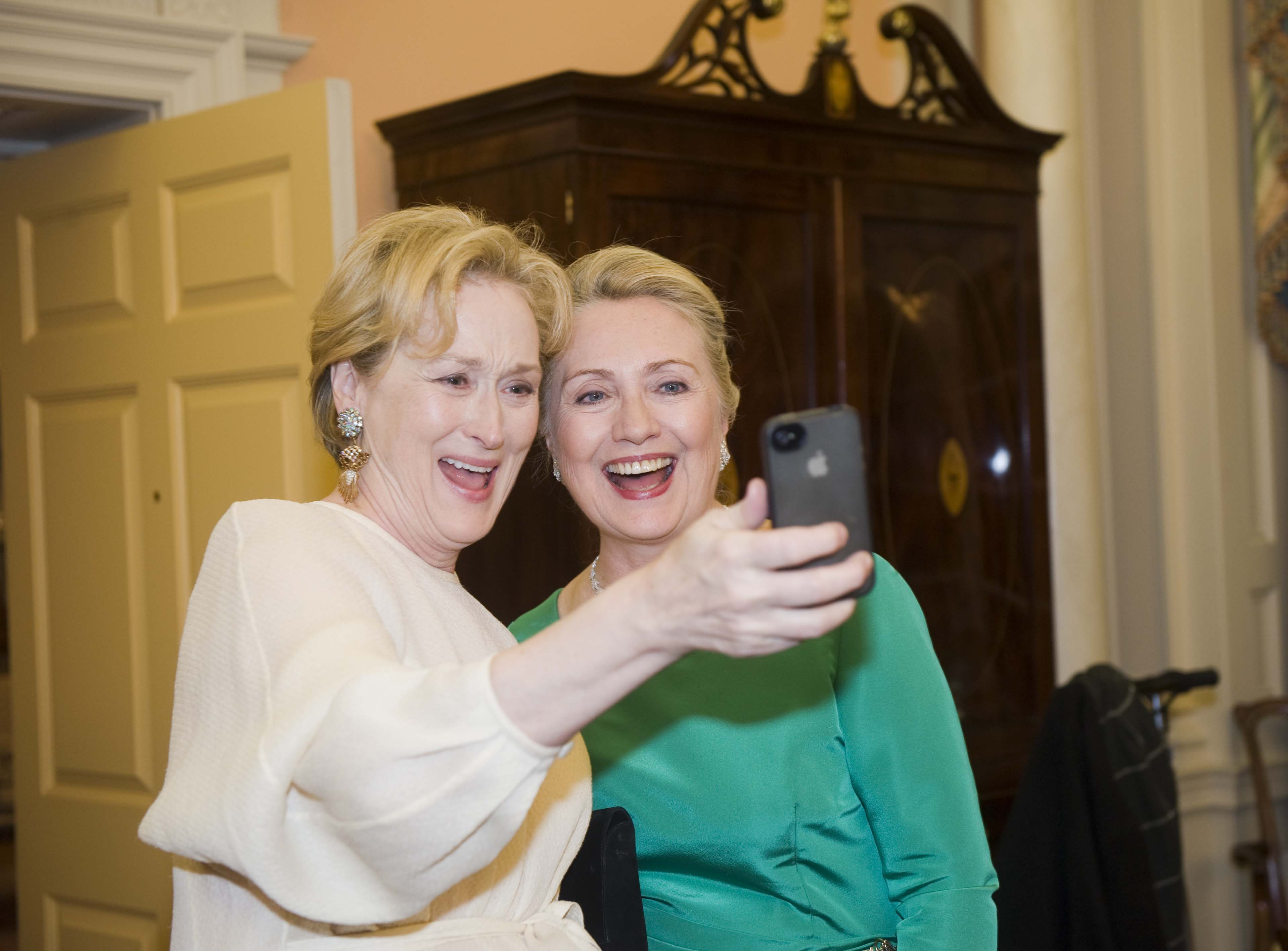 """File - In this Saturday, Dec. 1, 2012, file photo Actress Meryl Streep uses her IPhone to take a photo of her and Secretary of State Hillary Rodham Clinton following the State Department Dinner for the Kennedy Center Honors gala  at the State Department in Washington. """"Selfie"""" the smartphone self-portrait has been declared word of the year for 2013 by Britain's Oxford University Press. (AP Photo/Kevin Wolf, File)"""