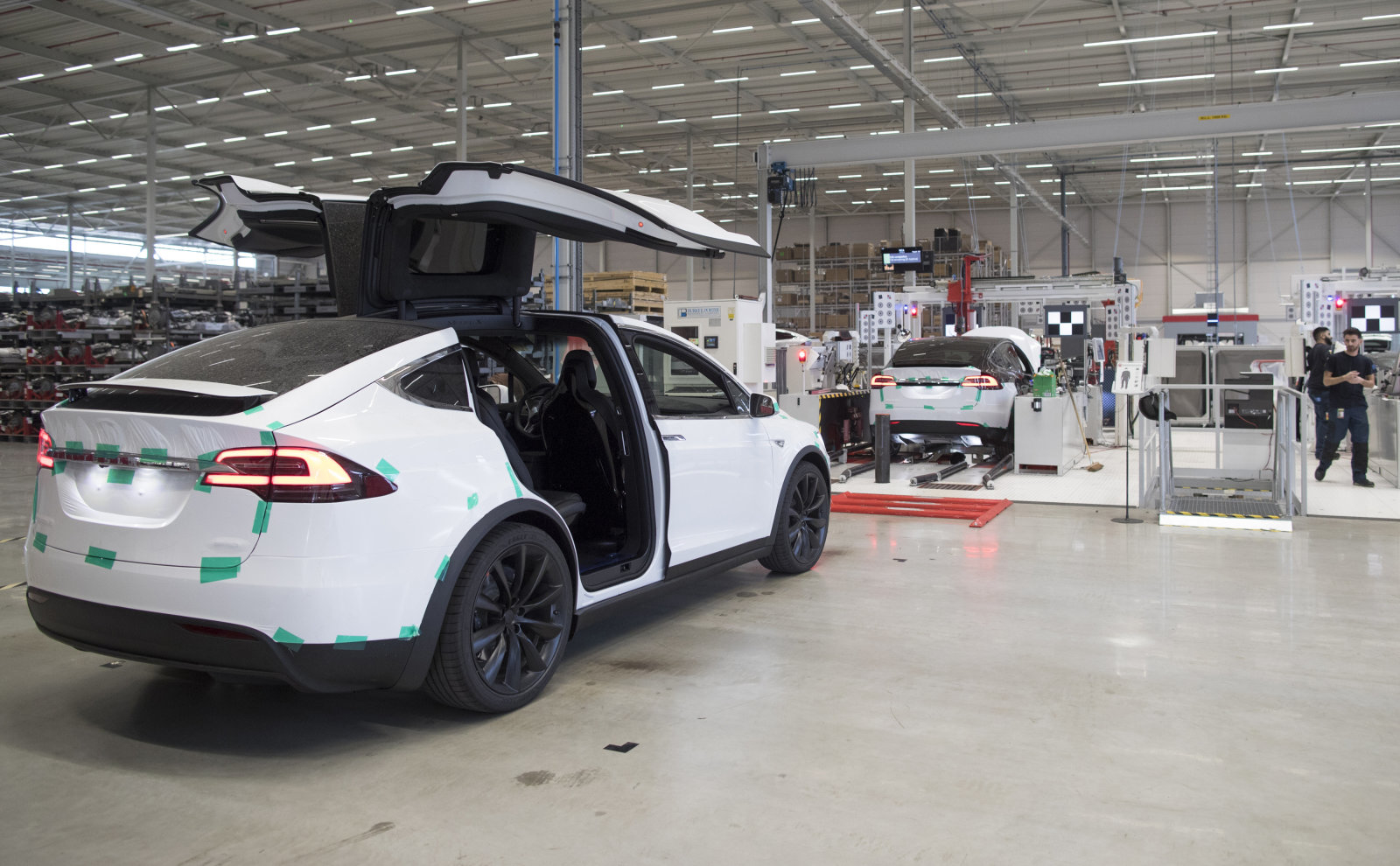 The rear gull wing doors of a Tesla Model X sports utility vehicle (SUV) sit open during assembly for the European market at the Tesla Motors Inc. factory in Tilburg, Netherlands, on Friday, Dec. 9, 2016. A boom in electric vehicles made by the likes of Tesla could erode as much as 10 percent of global gasoline demand by 2035, according to the oil industry consultant Wood Mackenzie Ltd. Photographer: Jasper Juinen/Bloomberg via Getty Images