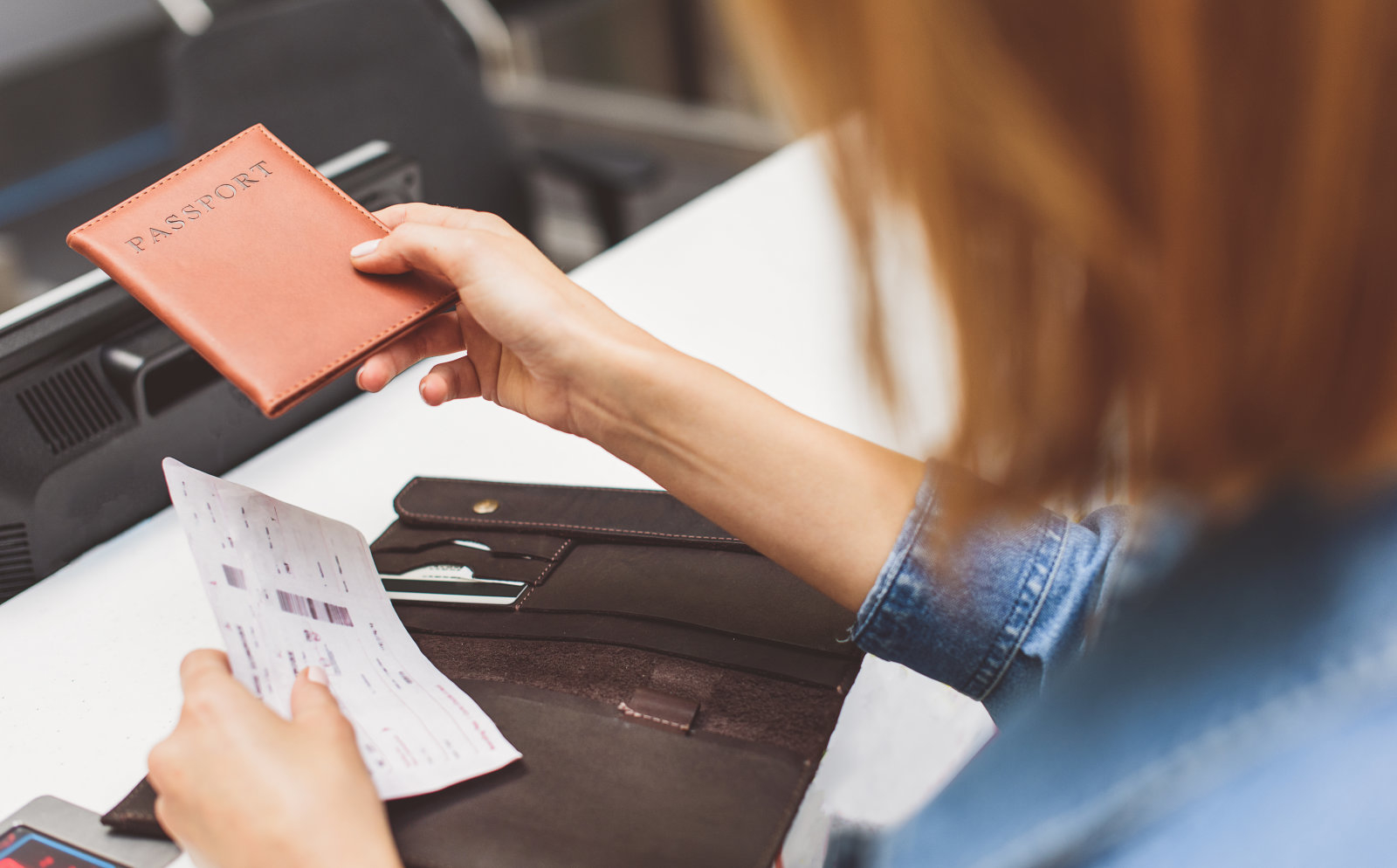 Young female passenger is giving her passport to check-in officer. Close up of her hands holding flight ticket