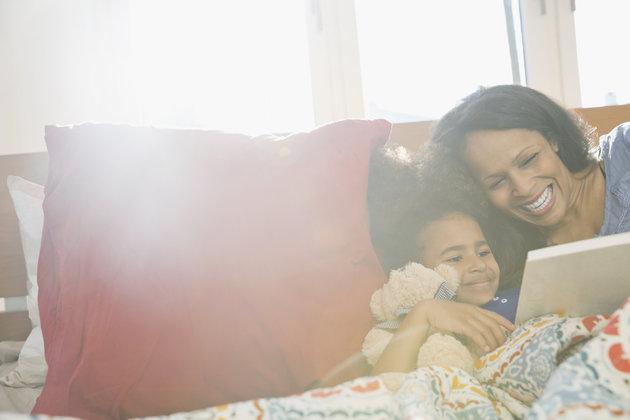 Una madre lee un libro a su