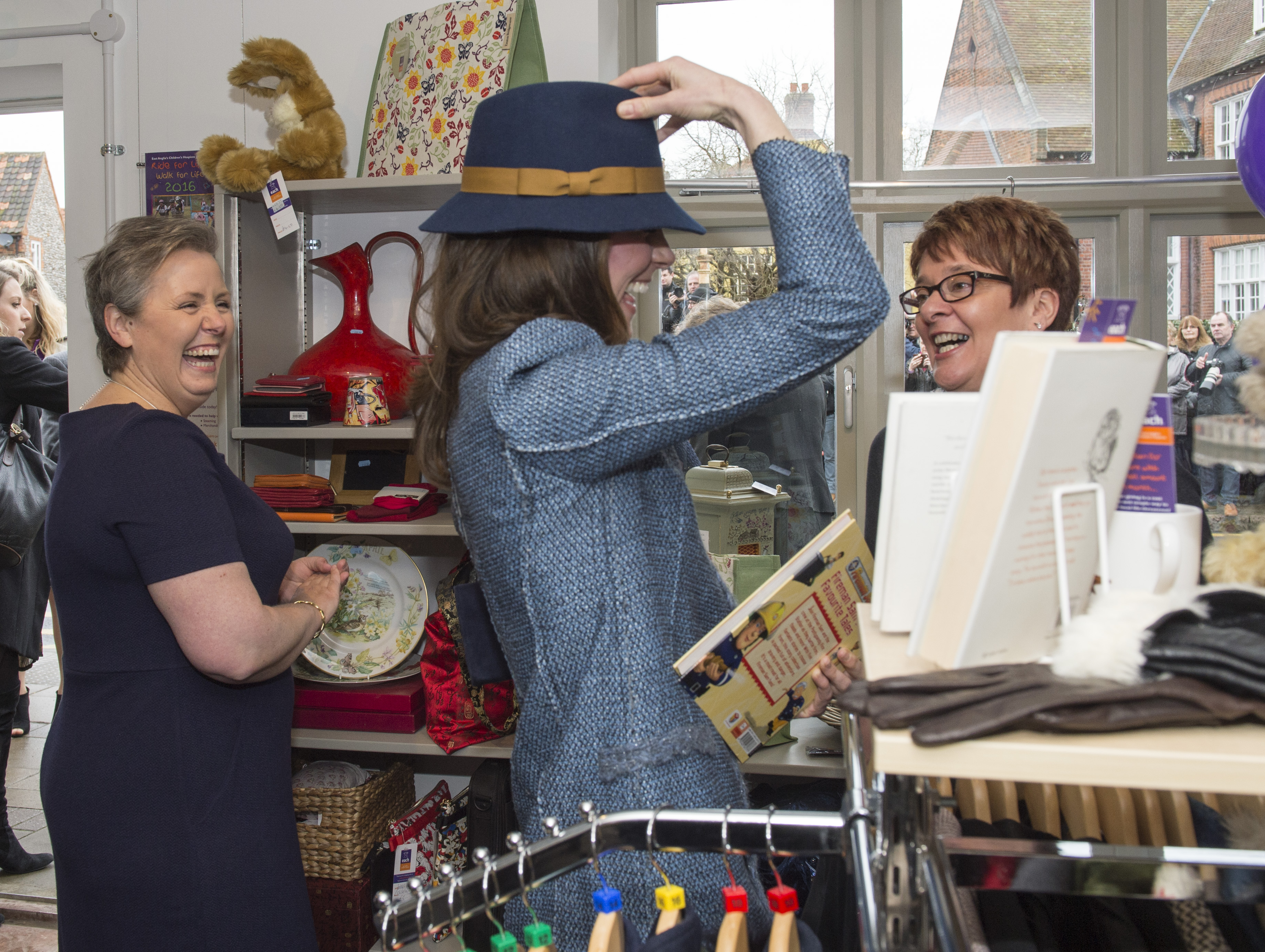 Britain's Kate, the Duchess of Cambridge, tries on a boden hat while a visit to officially open a new EACH charity shop.