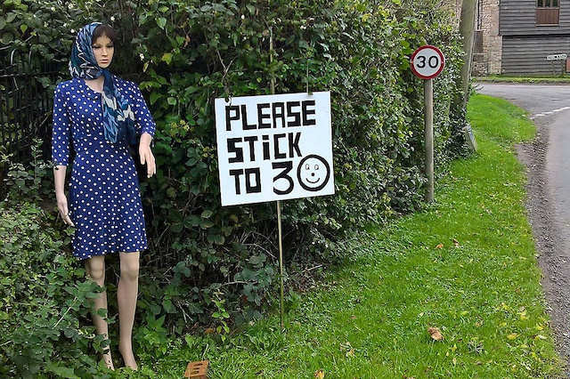 Betty the mannequin which is being used to stop speeding in a Gloucestershire village. See SWNS story SWDUMMY; Road safety campaigner Betty stands at the side of the road 24/7 in a bid to persuade drivers to stop speeding through a village on the Gloucestershire borders. Whatever the weather she waits on a bend to urge motorists to slow down and stick to the 30mph speed limit as they pass through Aston Ingham near Newent. But well-dressed Betty doesn't mind being outside around the clock because she is in fact a dummy standing guard on the B4221 between Kilcot and Lea.