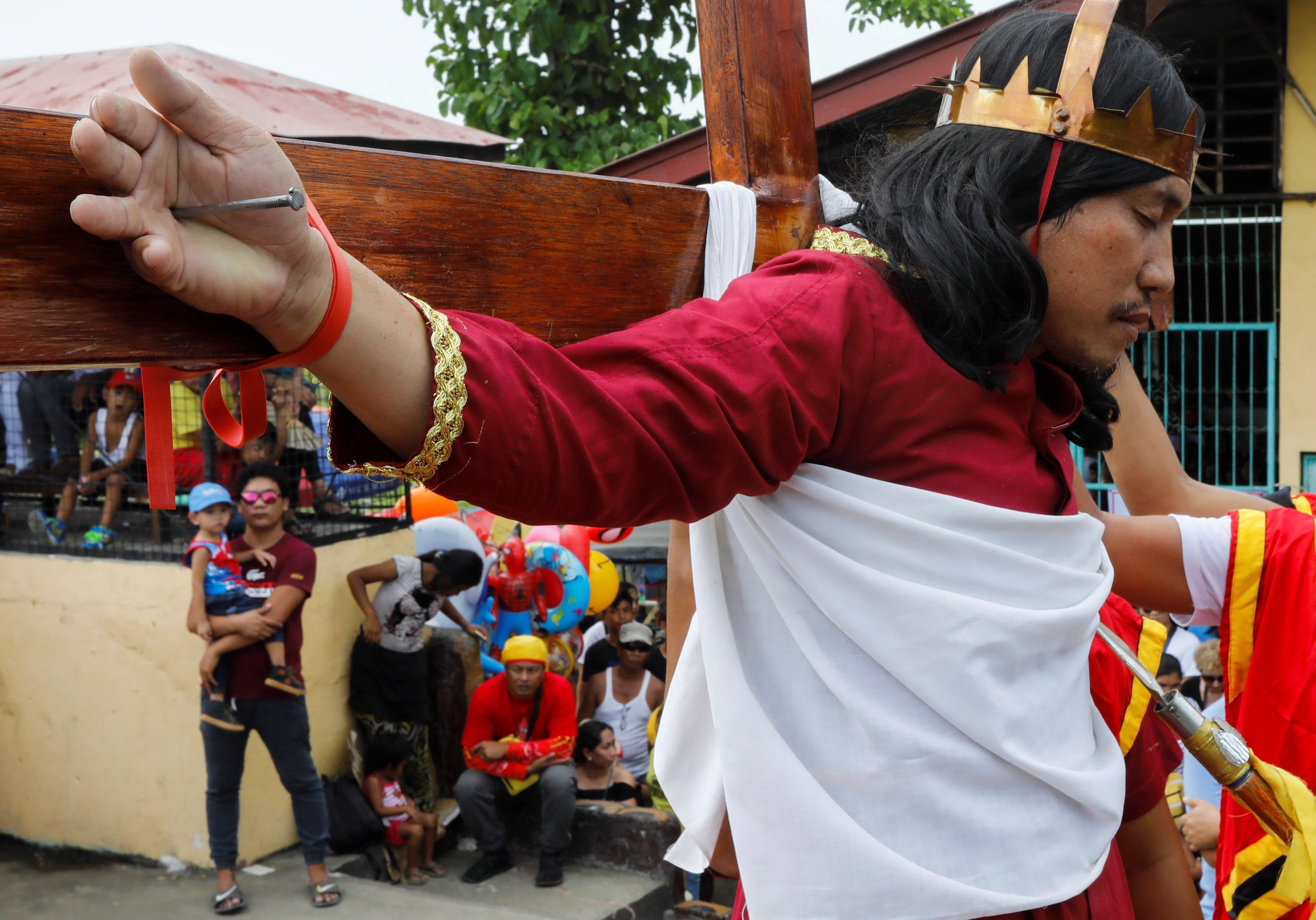 Un penitente filipino es clavado en una cruz en el distrito de Paombong, en la provincia de Bulacan,...