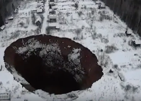 Holiday homes teetering over giant 250ft sinkhole