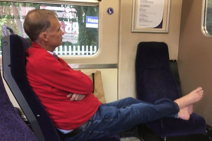 Commuter snapped with bare feet on train seat