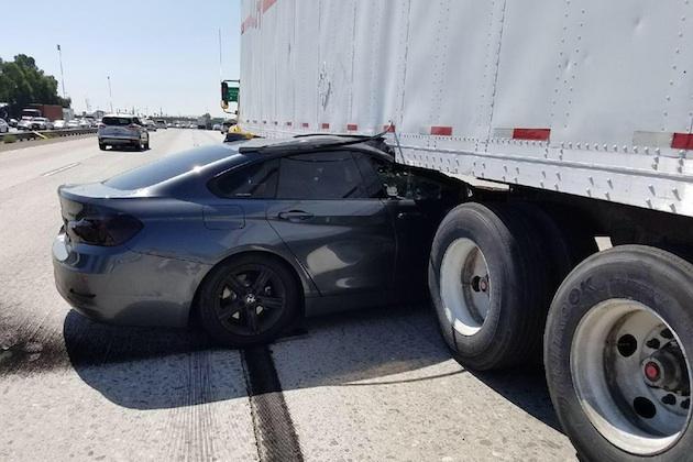 【車載ビデオ】高速道路で暴走ドライバーに当て逃げされたBMWが、トレーラーの下に巻き込まれる!