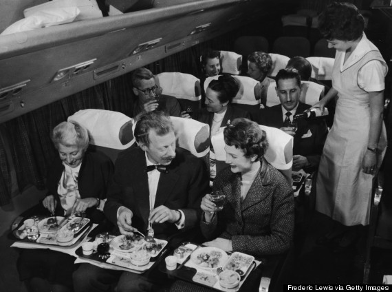 Interior view of a commercial passenger plane shows, in the foreground, a couple as they enjoy their...