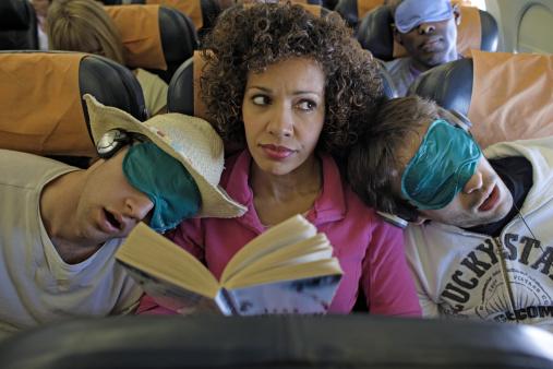 Woman sat on plane two men asleep on her shoulders