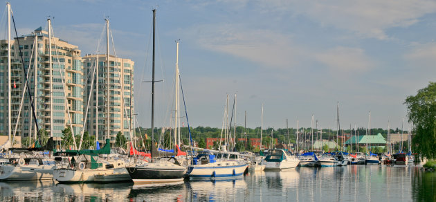 Barrie marina with condominium towers in the background. The sailboats or yachts are reflecting in the