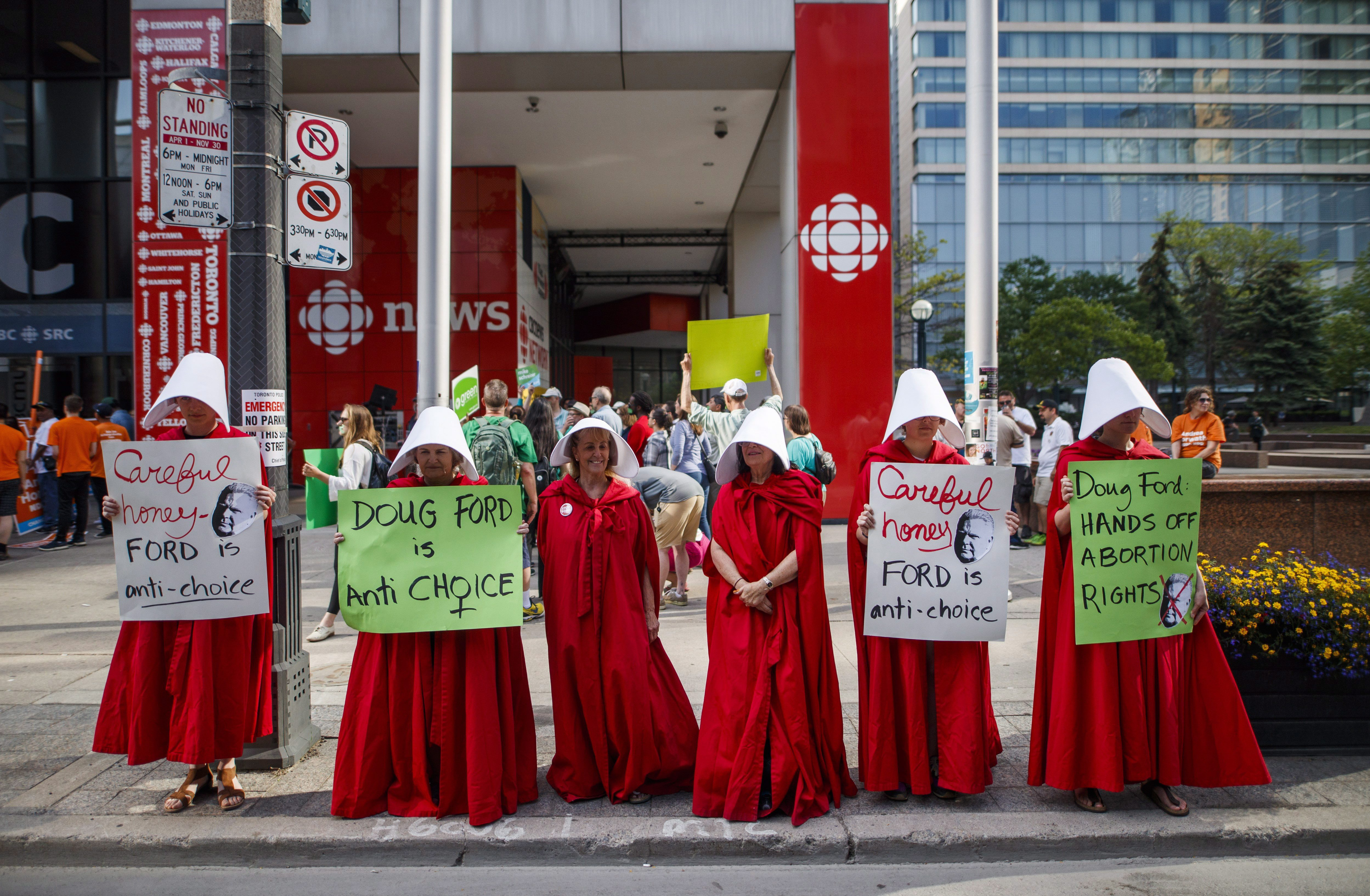 "Abortion rights activists dressed up as characters from ""The Handmaid's Tale"" hold signs ahead..."