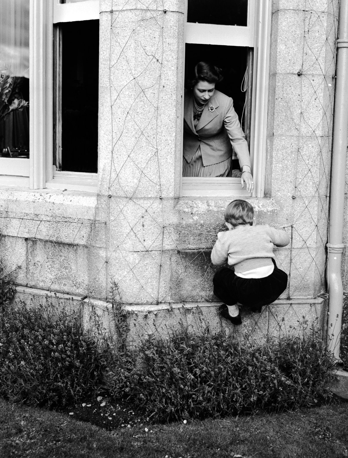 28th September 1952:  Princess Elizabeth helping Prince Charles to climb through a window at Bamoral Castle, Scotland.  (Photo by Lisa Sheridan/Studio Lisa/Getty Images)