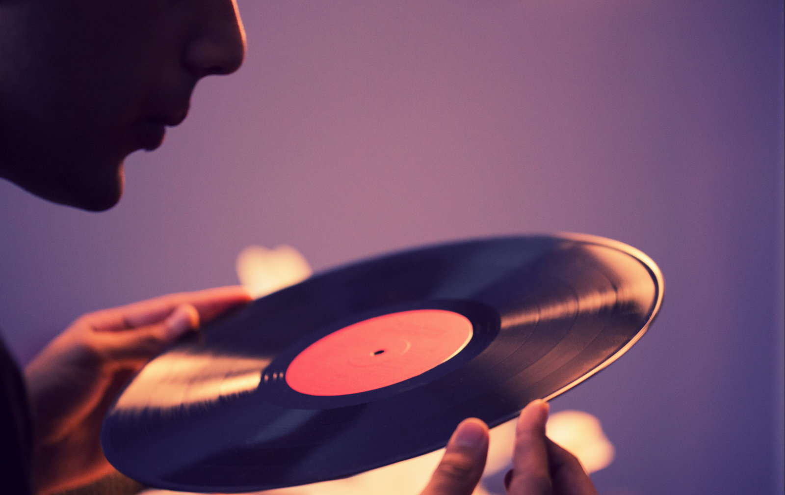 Man cleaning his old vinyls before playing them.