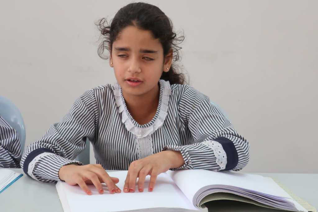 点字を読む難民少女。ガザにある視覚障害者のためのリハビリセンター(RCVI)で