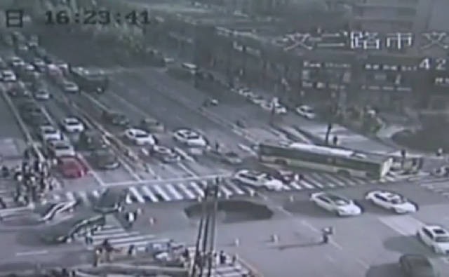 Watch as huge sinkhole opens up in middle of busy road