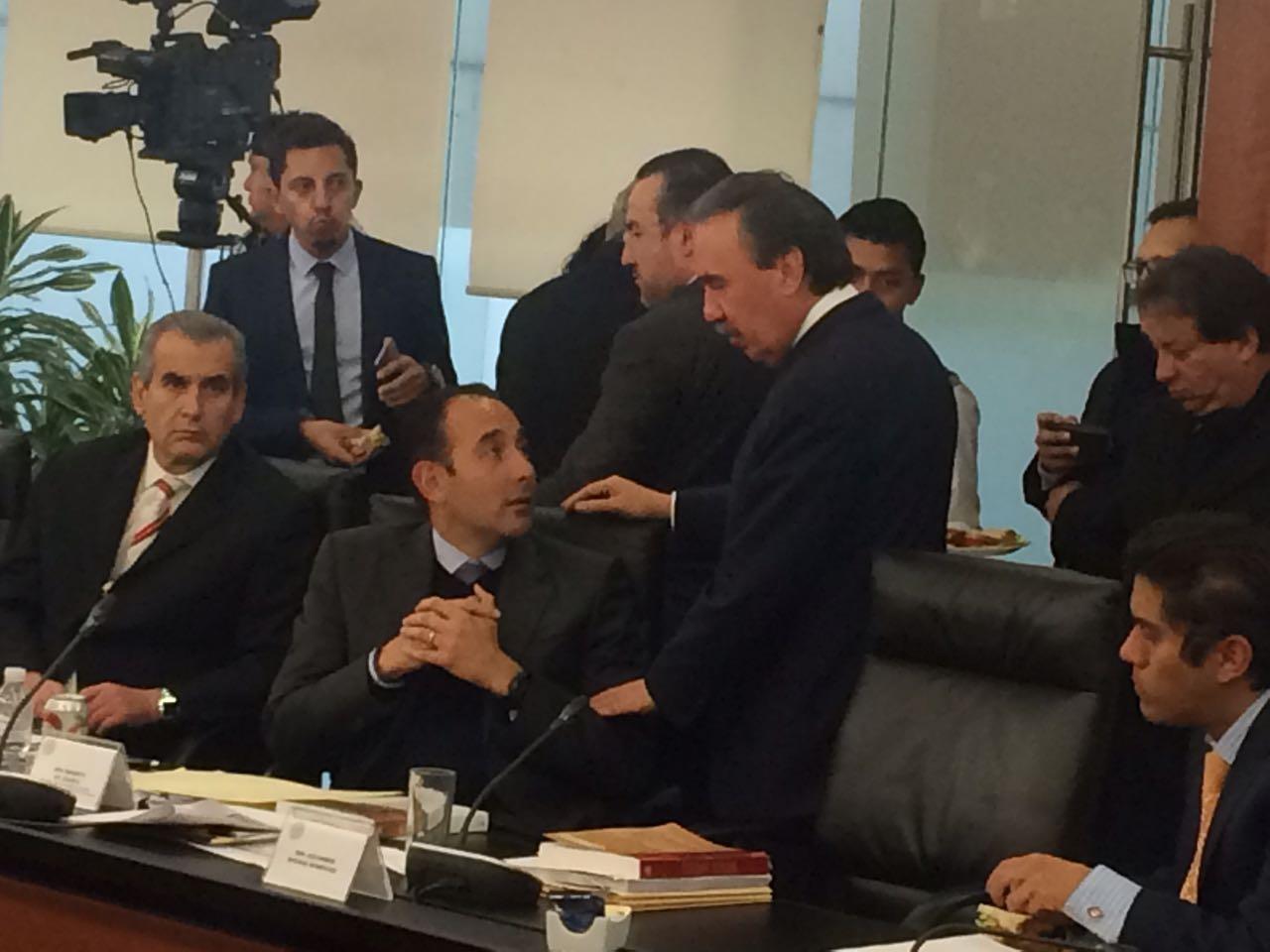 El senador Roberto Gil Zuarth, del PAN, habla con su colega, Emilio Gamboa, del PRI, mientras se discute...
