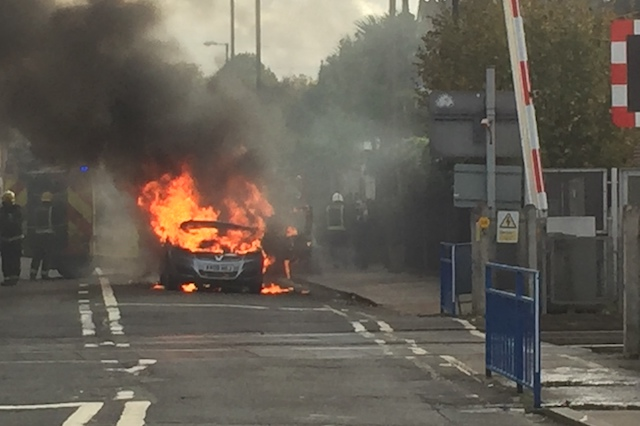 Firefighters extinguish a Vauxhall Zafira which caught light near a level crossing in Manor Road, south west London.
