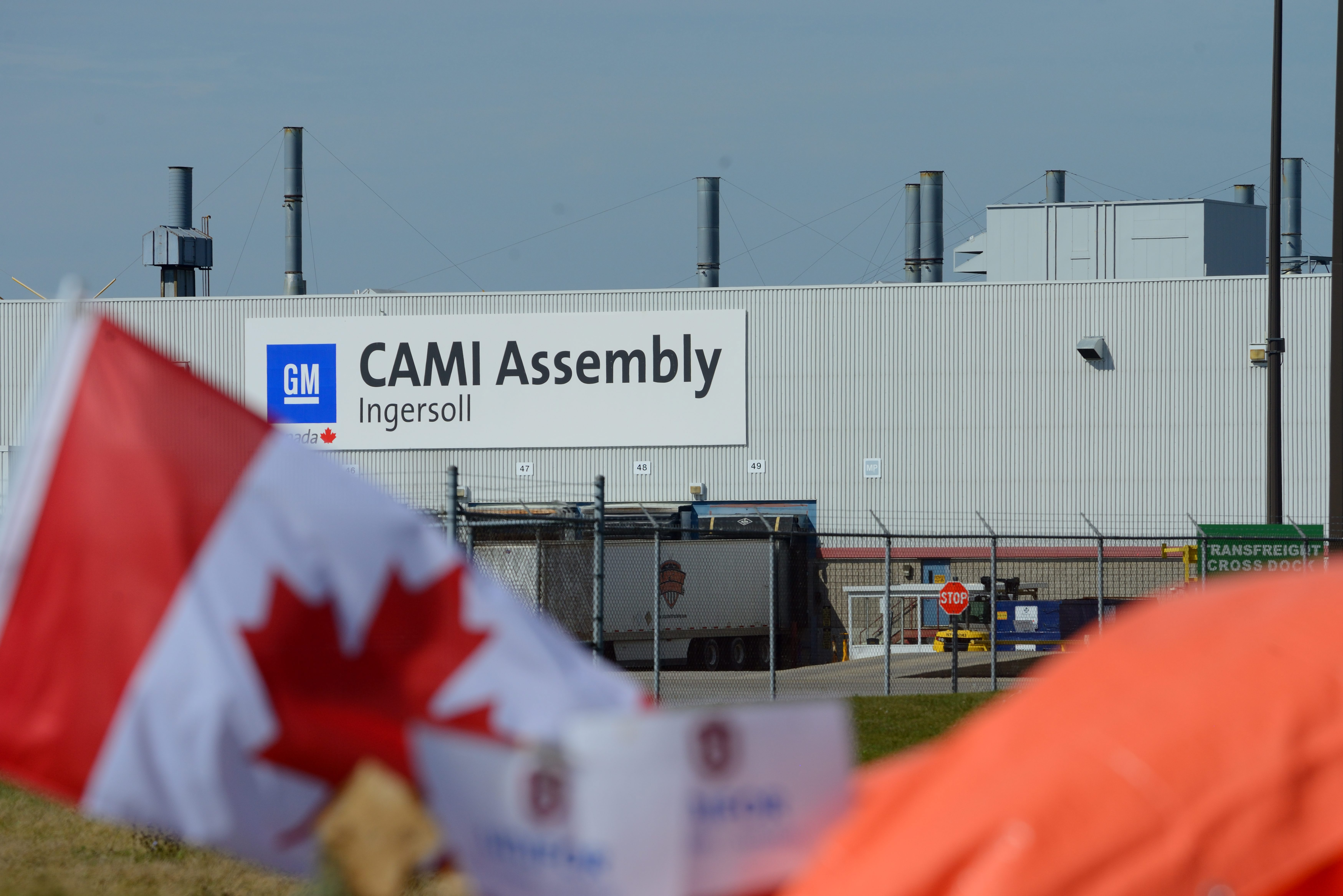A Canadian flag flies while workers represented by Unifor are on the picket lines of the General Motors...