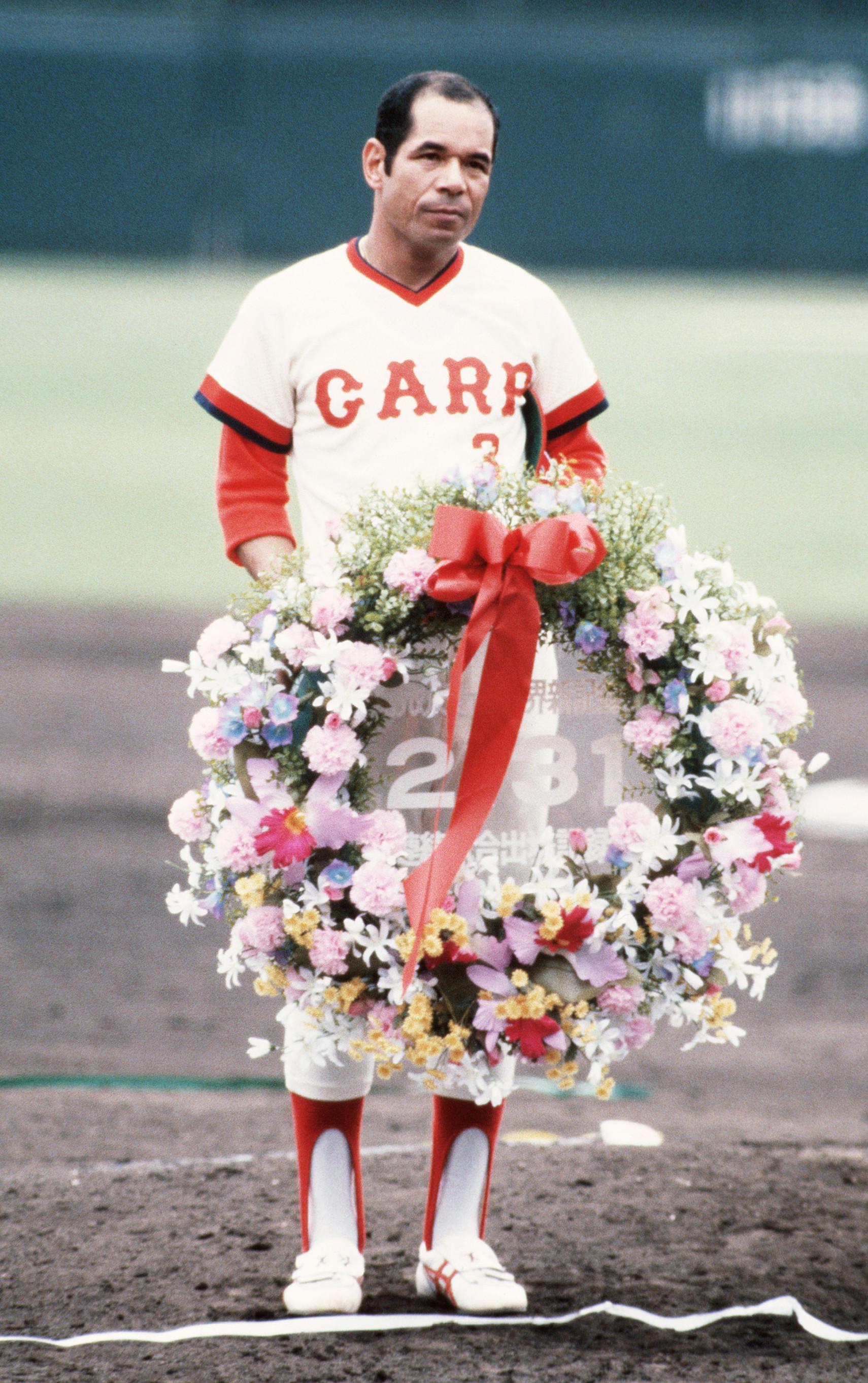 連続試合出場の世界新記録を達成し、グラウンドで記念の花輪を手にする衣笠祥雄選手=1987年6月、広島市