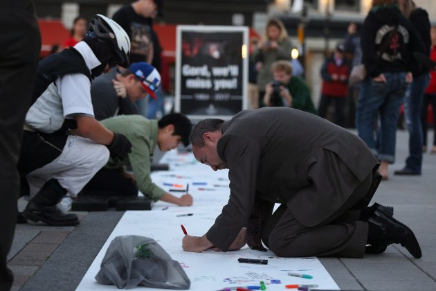 Kingston's Mayor Bryan Paterson writes messages for Gord Downie of the Tragically Hip on a banner in...