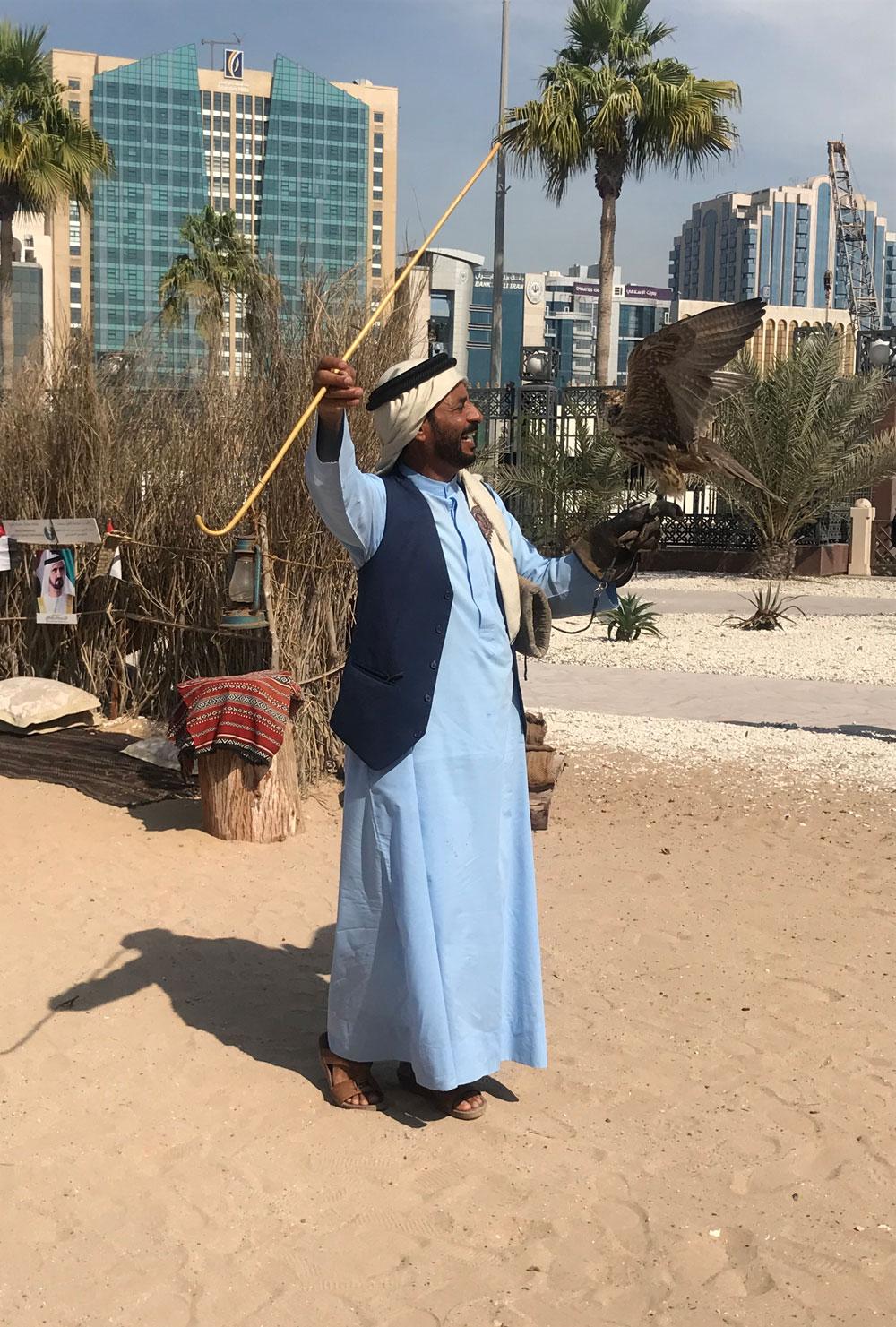 A man poses with his falcon in the historical Al Fahidi