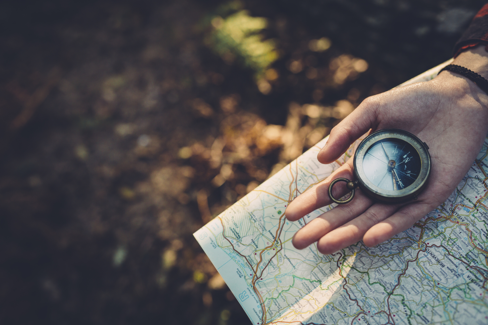 Hand holding a compass over a map