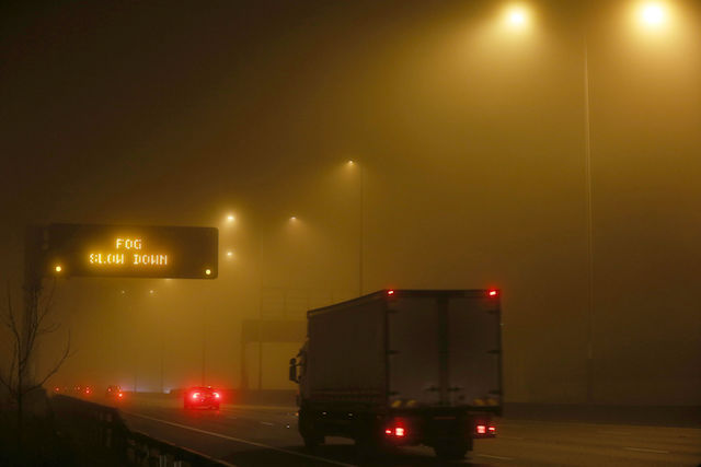 A sign on the M25 motorway near Heathrow Airport warns motorists of fog after forecasters warned of visibility as low as 100 metres with fog and sub-zero temperatures across swathes of England.