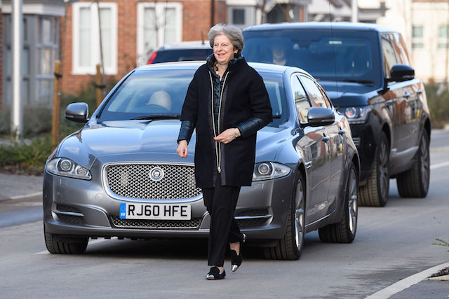 Prime Minister Theresa May walks from her car during a visit to a new housing development in Wokingham, Berkshire.