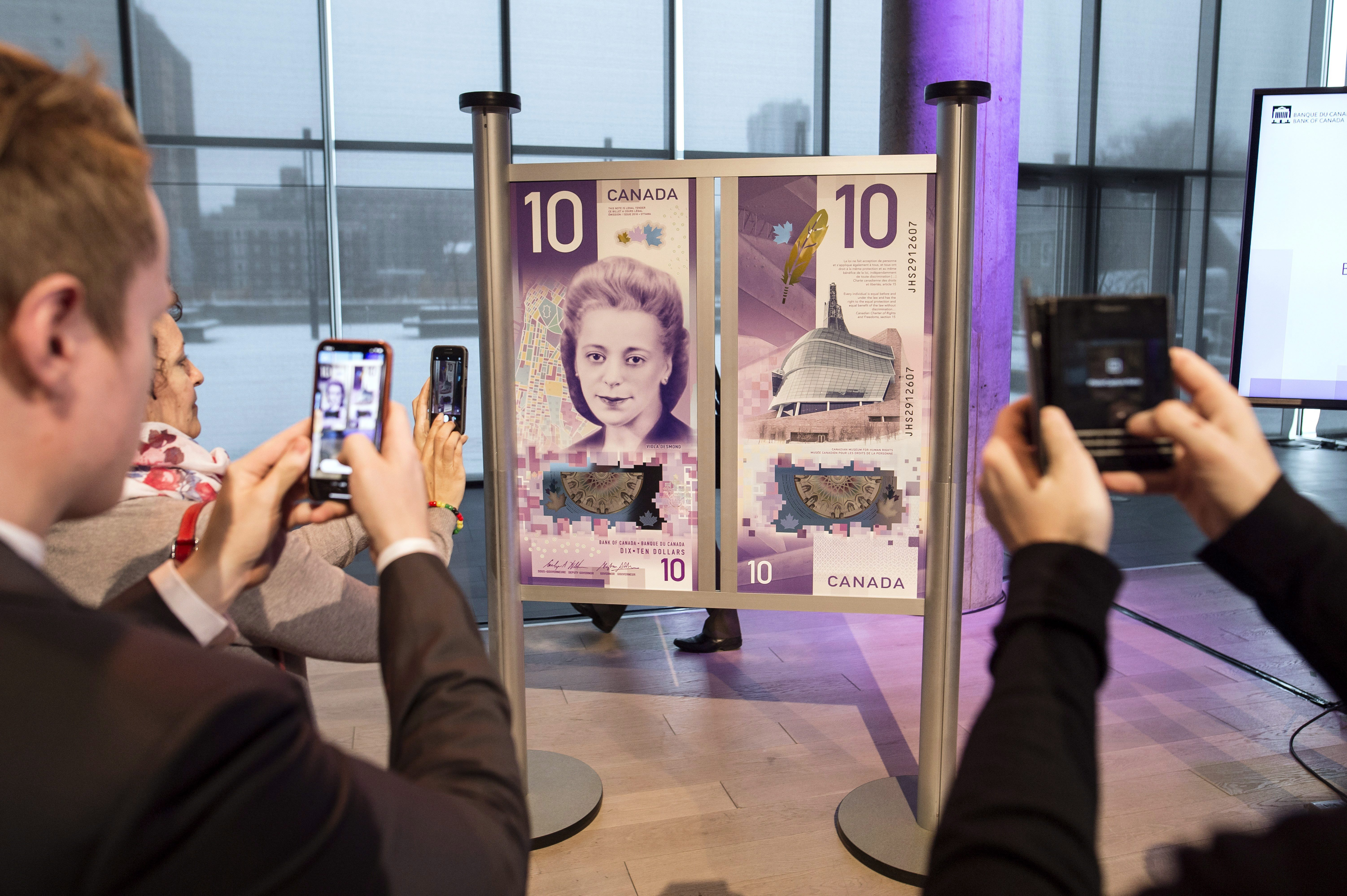 People take photos of the new $10 bank note featuring Viola Desmond following the bill's unveiling in...