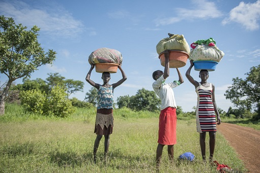 School-age girls in South Sudan carry heavy loads of washing to the river. Their household responsibilities...