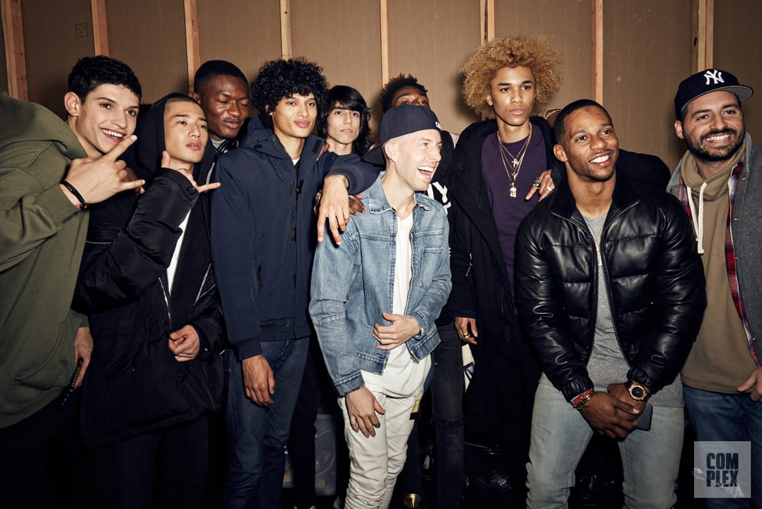 John Elliott backstage with his models, Victor Cruz, and Ronnie Fieg.