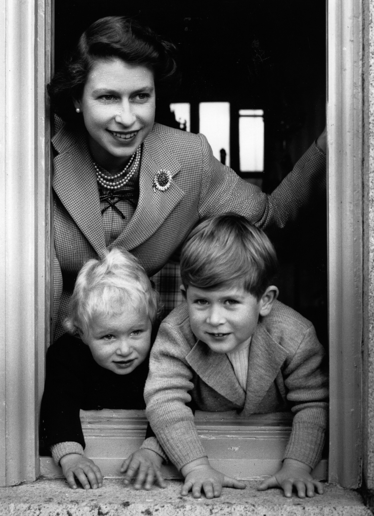 28th September 1952:  Queen Elizabeth II leaning out of a window with Princess Anne Elizabeth Alice Louise (left)  and Prince Charles Philip Arthur George.  (Photo by Lisa Sheridan/Studio Lisa/Getty Images)