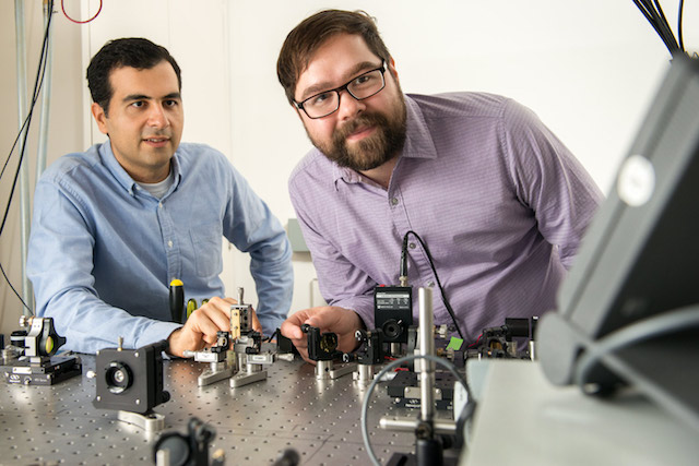 Alireza Marandi and Marc Jankowski with their experiment at the optical bench.