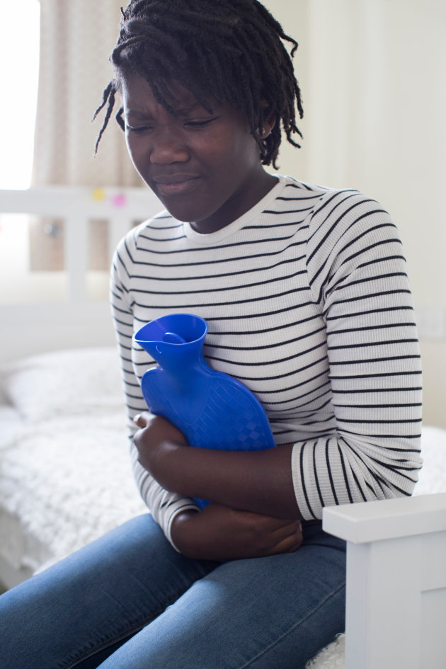 Teenage Girl In Pain Clutching Hot Water Bottle In