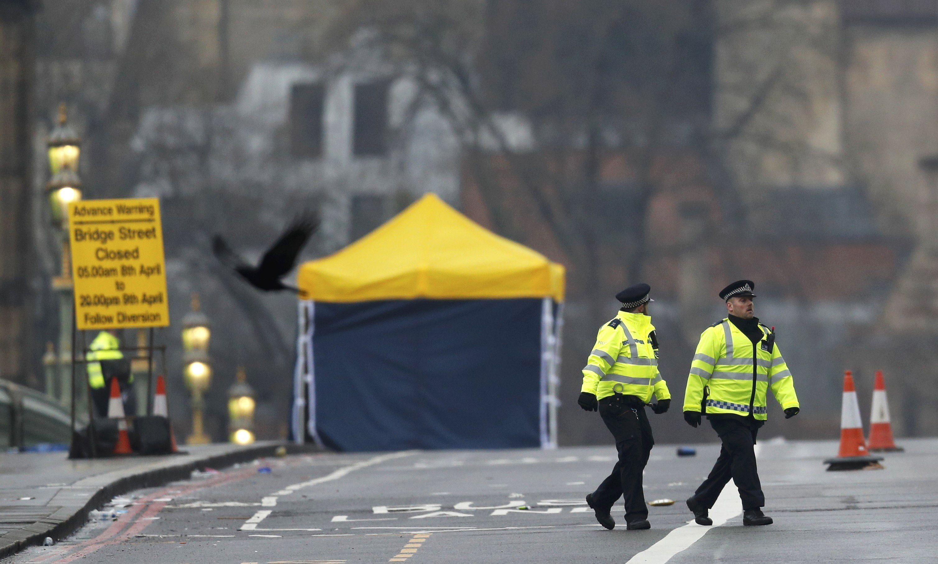 Police officers walk accross Westminster Bridge the morning after an attack by a man driving a car and...
