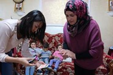 刺繍グループが自宅で作ってきた刺繍作品を点検するJVCエルサレム事務所の山村さんと刺繍グループのコーディネーターのマナールさん