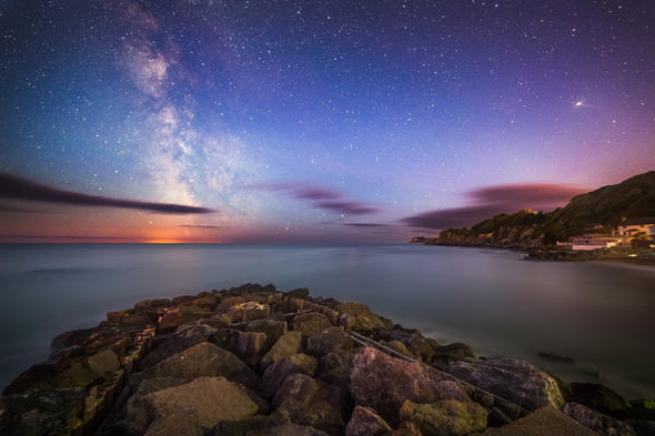 ISLE OF WHITE, GREAT BRITAIN - JUNE 23: A view of the Milky Way taken by Chad Powell on a DSLR camera on June 23, 2015, on the Isle Of Wight. A stones throw from Ventnor Botanic Garden, and an unspoilt hidden gem of the Island. It is also great for stargazing due to the limited amount of houses there and no street lights in the cove itself.  LIGHTS from the Milky Way dazzle above the Isle of White in these rarely seen British sky-scapes. Chad Powell captured images of spectacular light patterns above the familiar beach scenes of England?s largest island. The 23-year-old used a DSLR camera to enhance the Milky Way from the white strip visible to the naked eye into an explosion of colourful lights. The graphic designer from Ventnor, Isle of Wight, used the local architecture, coves and plant life of the island in the foreground of his photographs to create a contrast with the dramatic sky. Wheat fields, night daisies and a medieval lighthouse are some of the scenes Chad captures against the startling natural light displays.  PHOTOGRAPH BY Chad Powell / Barcroft Media  UK Office, London. T +44 845 370 2233 W www.barcroftmedia.com  USA Office, New York City. T +1 212 796 2458 W www.barcroftusa.com  Indian Office, Delhi. T +91 11 4053 2429 W www.barcroftindia.com