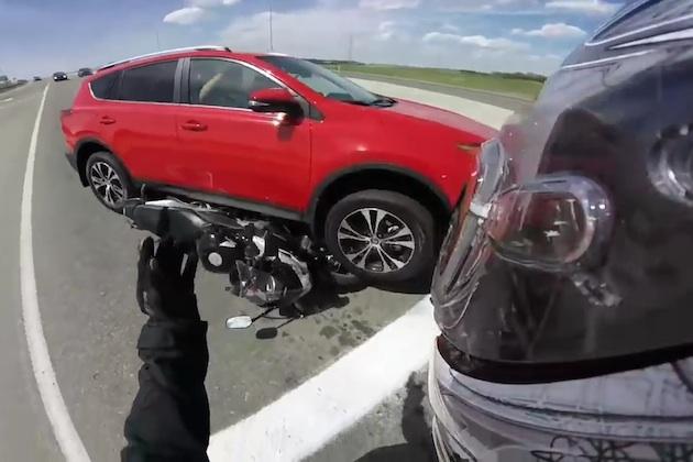 【ビデオ】交差点内で止まっていたSUVが突如猛スピードでバックし、オートバイを直撃!